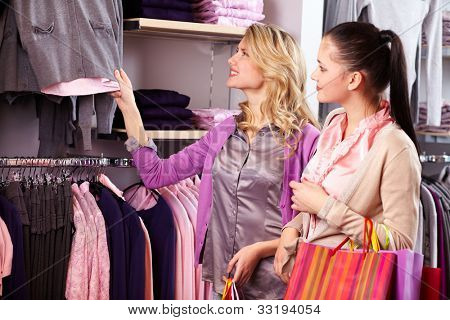 Image of two pretty girls looking at new collection of clothes in department store