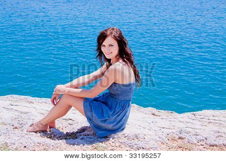 The girl on the rocks against the sea