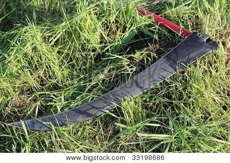 Scythe On Grass