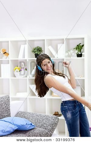 Teenager girl with smart phone dancing and listening music