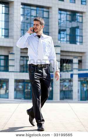 businessman talking on his cellphone while walking outdoors in front of a modern office building