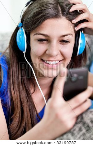 Smiling teenager girl looking in smart phone an listening music, close up
