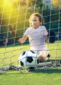 Soccer Ball In Goal On Green Grass. Disappointed Football Team Goalkeeper Following Goals. Goalkeepe poster