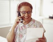 stock photo of housecoat  - Senior Hispanic woman talking on telephone - JPG