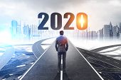 Rear View Of Businessman Standing On Tangled Road With 2020 Above It And Cityscape In Background. Co poster