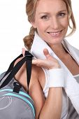 Woman post-workout with a gym bag and towel round her neck