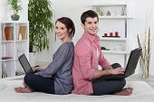 image of futon  - Couple sitting back to back and working on their laptops - JPG