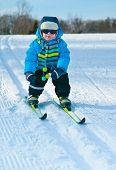 Cute little boy skiing downhill