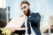 Portrait Of A Bearded Businessman Feeling Hungry And Surprised While Opening Pizza Box Outdoors poster