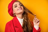 A Girl With Curls, Red Lipstick In A Red Coat And A Beret Is Standing On A Yellow Background, Twirli poster