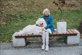 Happy Adult Woman Resting With Cute Pedigree Dog poster
