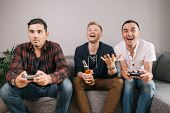Joyful Young Men Playing Video Game Console. Three Friends Playing Video Game On Home. Young Man Exc poster