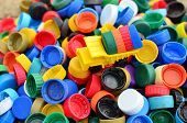 Dump Truck Unloads Colorful Plastic Caps.  Concept For The Collection, Recycling Of Plastic Bottle C poster