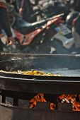Fried Potatoes In A Large Frying Pan. Grilled Vegetables On Motorcycle Festival Background. Blurred  poster