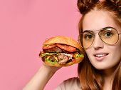 Stylish Red-haired Young Girl Hold A Big Barbecue Sandwich With A Hungry Mouth Laughing On A Pink Ba poster