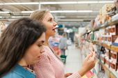 Shopping At The Grocery Store. Two Young Women Brunette And Blonde Choose Products In The Store. In  poster