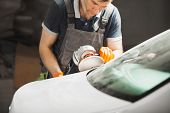 Man Polishes White Car In Auto Repair Shop, Close-up. Orbital Polishing Machine. Polished Finishing. poster