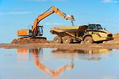 image of movers  - wheel loader excavator machine loading dumper truck at sand quarry - JPG
