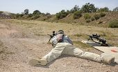 stock photo of prone  - Shooter laying on the ground taking a shot at a target at 100 yards - JPG