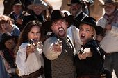 stock photo of gunfighter  - Three gunfighters yell while shooting in outdoor old west scene - JPG