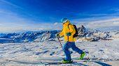 Man skiing on fresh powder snow with Matterhorn in background, Zermatt in Swiss Alps. poster