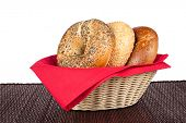 A wicker basket with three bagels including an onion bagel, sesame seed bagel and a wholegrain wheat