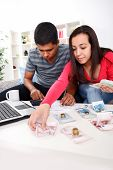 Young couple calculating their domestic bills at home poster