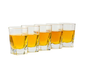 stock photo of shot glasses  - Five shot glasses with alcohol drink isolated at white background - JPG