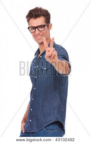casual young man showing victory sign with his other hand in his pocket while smiling to the camera. isolated on a white background