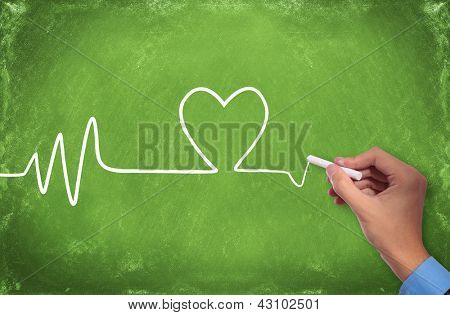 man drawing a heart pulse trace on a green chalkboard