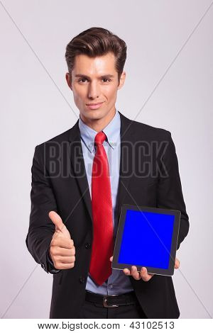 young business man presentig tablet and showing thumb up, on gray background