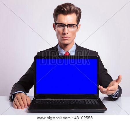 picture of a serious young business man presenting you a laptop, on gray background