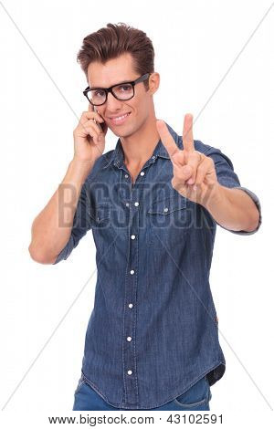 casual young man showing victory sign while on the phone and smiling to the camera. isolated on a white background