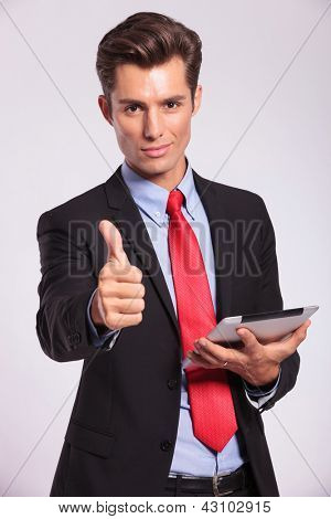young business man holding a tablet pad and making the ok thumbs up gesture on gray background