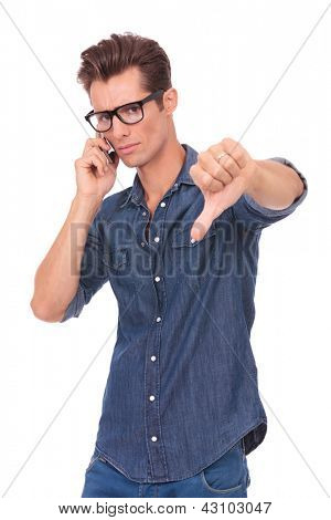 casual young man receiving some bad news over the phone and showing thumbs down. isolated on a white background