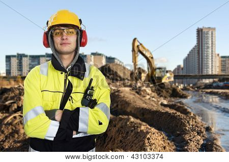 Young construction engineer posing in front of the muddy construction site of a large building project
