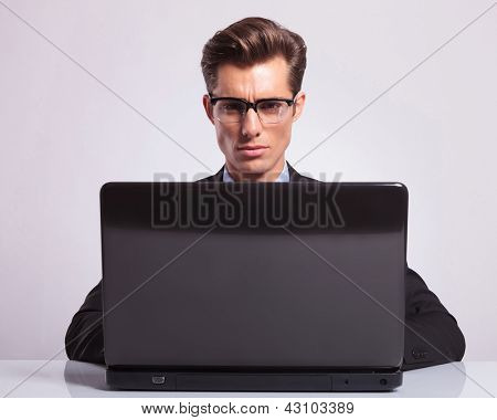 close-up picture of a young attractive business man working at his laptop and looking into the camera, on a gray background