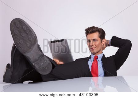 handsome young business man reading on his tablet, sitting relaxed with a hand at the back of his head and his legs on the desk, over gray background