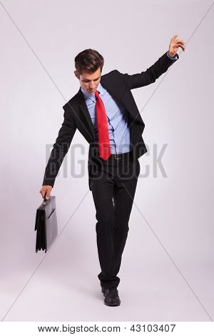 Business man holding a briefcase balancing and walking forward on an imaginary rope on gray background