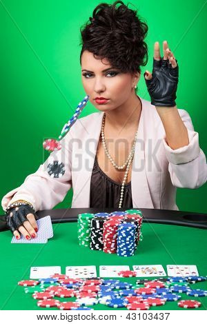 sexy young lady throwing some chips at the poker table, raising or calling you, looking at the camera with a poker face. on green background
