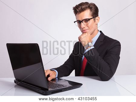 young business man at the laptop looking at the camera while holding hand on his chin