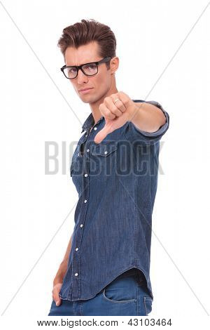 casual young man showing thumbs down sign and holding a hand in his pocket while looking at the camera with a serious look on his face. isolated on a white background