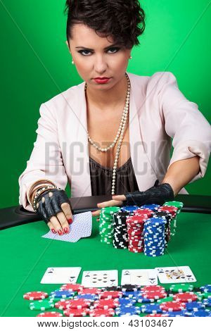 daring sexy woman goes all in after seeing her poker hand, with a challenging look on her face. on green background