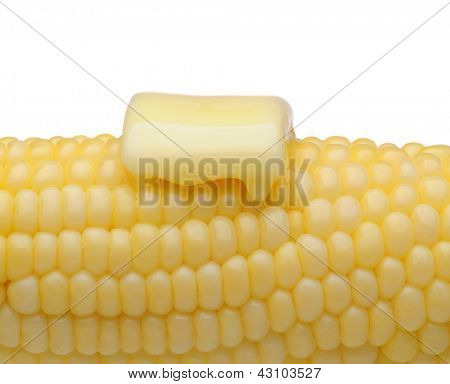 Closeup of an ear of corn with a pat of melting butter. Horizontal format on white.