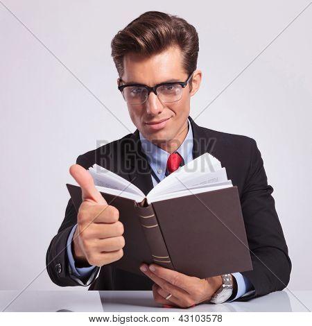 empresario joven atractivo sentado en el escritorio con un libro en la mano y mostrando los pulgares cartel
