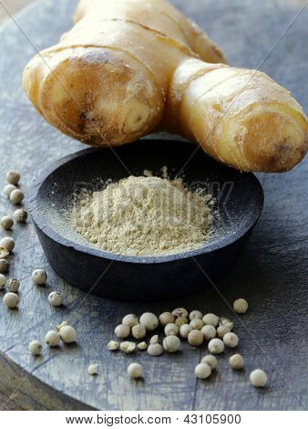 ground ginger (spice) and fresh on a wooden board