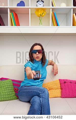 amazed young woman in stereo glasses holding a TV remote control
