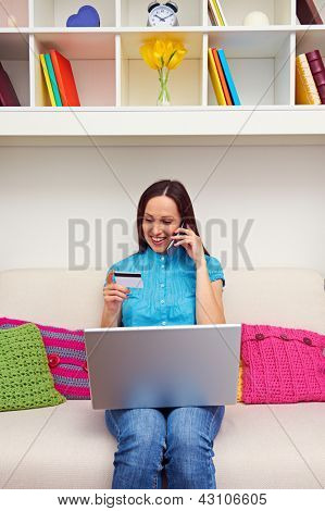 smiley woman looking at credit card and talking on the phone
