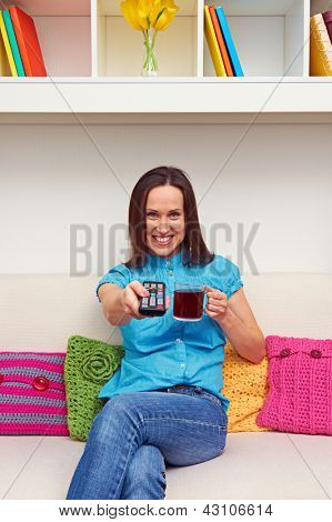 smiley young woman holding cup of tea and remote controller