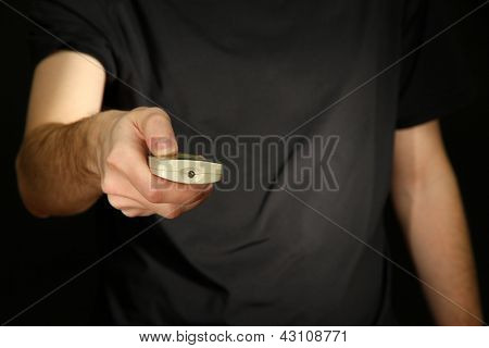 Man hand holding a TV remote control, on dark background